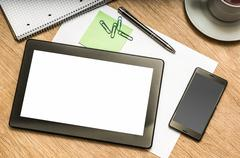 Digital tablet with blank screen and mobile phone on wooden table in office Kuvituskuvat