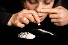 Junkie woman snorting cocaine powder with rolled banknote on black background Kuvituskuvat