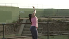 Dancer warms up with a barre exercise routine in an industrial environment Stock Footage