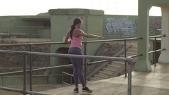 African American alternative woman performs barre exercises in a run down area Stock Footage