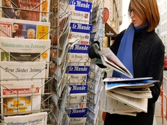 Woman purchases a Les Echos French newspaper from a newsstand Stock Footage