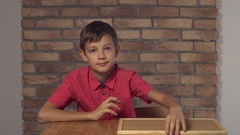 Schoolboy sitting at the table with flip chart Stock Footage