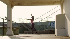 Ethnic dancer practices a choreographed ballet routine in an urban setting Stock Footage
