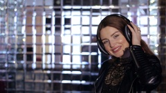Happy girl in a luxurious dress with stereo headphones. Arkistovideo