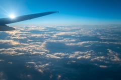 The plane fly in the sky with cloud on the background of bright sun Stock Photos