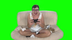 Man gamer playing videogames with gamepad sitting on dirty couch Stock Footage