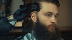 Young handsome barber making haircut of attractive bearded man in barbershop Stock Footage