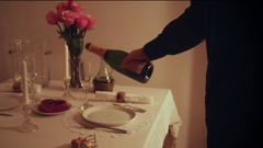Pouring Champagne into Empty Glass on Romantic Dinner Table Setting Stock Footage