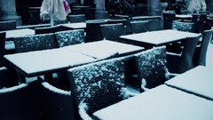 Street cafe tables in the snow. Low season concept. 4K steadicam video Stock Footage
