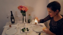 Beautiful Elegant Woman lighting Candles with matches at romantic dinner Stock Footage