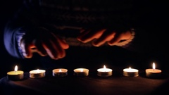 Wizard conjure with hands above burning candles Stock Footage