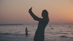 Woman photographed themselves on the phone while standing on the beach Stock Footage
