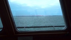 View of calm turquoise sea and coast through window of ship. Clear day Stock Footage