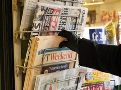 Woman purchases a Financial Times Ft Weekend British newspaper from a newsstand Stock Footage