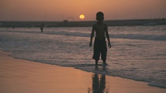Single child - Arab or Indian boy - standing in water and playing on the beach Stock Footage