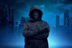 Hooded man with anonymous mask standing Stock Photos