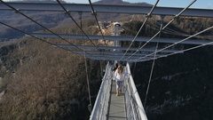 Woman walk thru high bridge over the canyon at SkyPark AJ Hackett Sochi Stock Footage