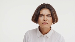 Young beautiful brunette east asian female in shirt looking suspiciously at Stock Footage
