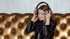 Beautiful brunette in evening dress listening to music with headphones. Stock Footage