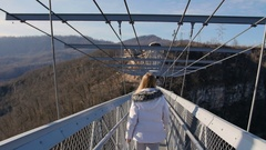 Woman walk thru high bridge over the canyon and gesture follow me Stock Footage