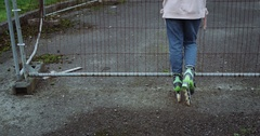 Back detail of girl legs on roller skates near rusty metallic fence. Girl Stock Footage