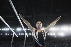 Male gymnast with arms raised next to parallel bars Stock Photos
