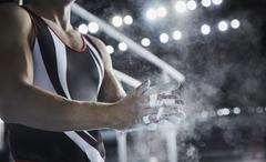 Male gymnast rubbing chalk powder on hands below parallel bars Stock Photos
