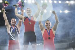 Enthusiastic male gymnasts celebrating victory on winners podium Stock Photos