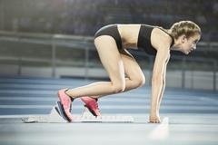 Focused female runner ready at starting block on sports track Stock Photos