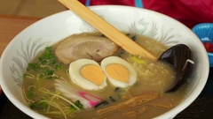 Hand eating hot Japanese ramen, black noodle with boiled egg in flavorful soup Stock Footage