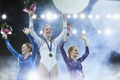 Female gymnasts celebrating victory waving on winners podium Stock Photos
