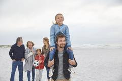 Multi-generation family walking on winter beach Stock Photos