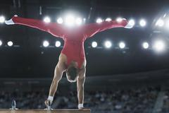 Male gymnast performing upside-down handstand on pommel horse Stock Photos