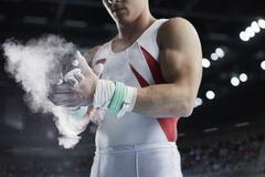 Male gymnast applying chalk powder to hands Stock Photos