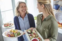 Smiling mother and daughter serving food Stock Photos