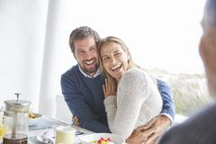Happy affectionate couple laughing and hugging at patio breakfast Stock Photos