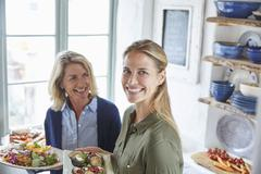 Portrait smiling mother and daughter serving food Stock Photos