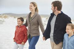 Family holding hands walking on winter beach Stock Photos