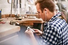 Male jeweler using calipers and listening to music with headphones in workshop Stock Photos