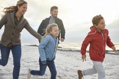 Playful family running on winter beach Stock Photos