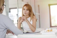 Attentive businesswoman listening to colleague in meeting Stock Photos