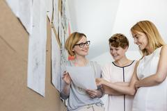 Smiling female designers reviewing proofs at bulletin board in office Stock Photos