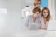 Businesswomen working at laptop and digital tablet in conference room meeting Stock Photos