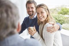 Smiling affectionate couple hugging and drinking coffee on patio Stock Photos