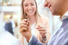 Jeweler helping man shopping for diamond ring in jewelry store Kuvituskuvat