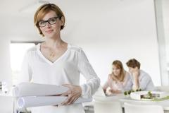 Portrait confident female architect holding blueprints in conference room Stock Photos