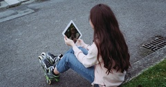 Amazing detail of young girl with beautiful hair sitting on street , holding Stock Footage