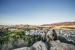 Couple sitting on rocks overlooking landscape, Athens, Greece Stock Photos