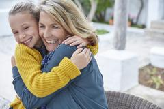 Enthusiastic grandmother and granddaughter hugging on patio Stock Photos