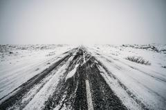 Diminishing perspective remote snow covered road Stock Photos